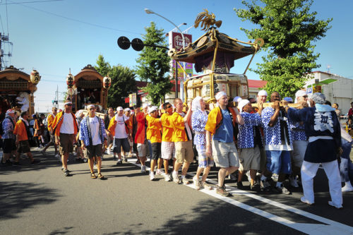 YOKOTA AIR BASE, Japan -- Military members from Yokota Air Base, Japan, sing and carry a Mikoshi (shrine) during the Fussa Tanabata Festival Aug. 6. The festival itself featured a number of different groups carrying Mikoshi shrines and mobile stages featuring performances of traditional Japanese characters such as a fox and an Oni, or a demon. At many points during the march the carrying groups would raise the shrines and cheer in front of the stages. The festival included performances of traditional Japanese dancing and the carrying of Mikoshi from Shinmeisya Shrine to Fussa City Hall. (U.S. Air force photos by Staff Sgt. Stacy Moless)