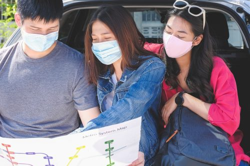 Young asian traveler friends group wearing face mask and looking at the map for plan a trip during sitting in trunk of hatchback car. New normal travel concept.