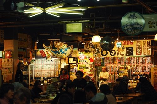 Kochi, Japan, 7 January 2019; Inside of Hirome market, indoor village of food and stalls. Menu signs in front of shops. People enjoy fresh food and drink together at common tables.