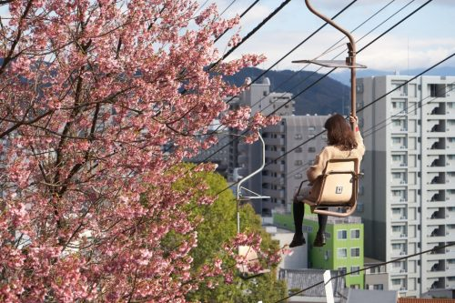 The young woman sat in the ropeway of single person to the Matsuyama Castle. Sakura cherry blossoms full blooming. Shot in Matsuyama City, Ehime Prefecture, Japan.