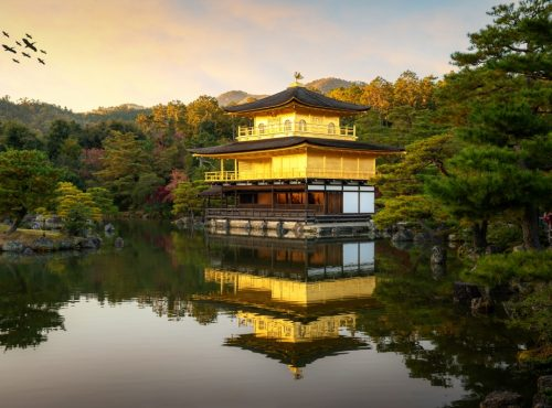 View of Kinkakuji the famous Golden Pavilion with Japanese garden and pond with dramatic evening sky in autumn season at Kyoto, Japan. Japan Landscape and nature travel, or historical building.